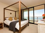 The four poster king size bed in the master bedroom looks out to sea