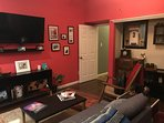 Living room with record player, mini bar, tv and pullout couch.