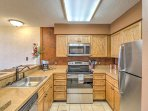 Step inside the open-concept, fully equipped kitchen, which features large countertops and modern stainless steel...