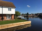 Newly laid lawn with recently quay headed mooring and Wroxham bridge, the centre of the Broads.