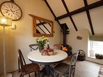 Dining table in front of a welcoming woodburner