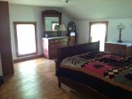 Upstairs: Bedroom with full-sized bed, includes a small TV.