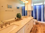Freshen up in this pristine bathroom, equipped with a tub-shower combo and double vanity.