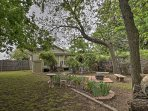 Spend time relaxing in the shaded backyard with tall trees, fire pit, and bench seating.