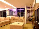 The spacious living room with a sectional sofa has a big 52'  3D  TV with cable.