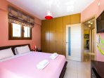 main bedroom with queen size bed and flat TV 32' wall mounted