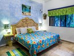 Bedroom has a king size bed and faces swimming pool area