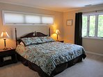 Upstairs Lakeside Bedroom. King bed, flat screen TV and view of the lake and mountain.