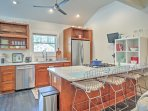 This fully equipped kitchen features stainless steel appliances, granite countertops, and bar top seating.
