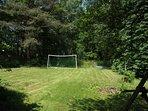Far end of the garden with a football net & bonfire area, backing onto woodland