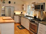 modern, well-equipped kitchen w/ granite counters, island and Jenn-Aire appliances