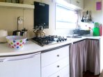 Kitchenette with gas hob, prep bowl, under counter fridge, toaster, kettles and coffee plunger