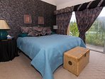 King bed in master bedroom has a 180 degree lake view