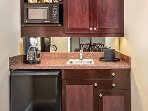 Hotel style kitchen with microwave, refrigerator, coffee maker and sink.