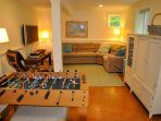 downstairs rec-room with foosball table, TV and sectional with full-size sleeper