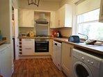 Bright kitchen with washing machine, dishwasher, tumble dryer, two fridges, freezer and gas hob