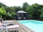 Heated swimming pool, surrounded with wooden decking,  with gazebo and fig tree shaded sitting area.