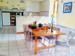 Bright open plan dining room with 8chairs. Behind is fully equipped kitchen