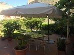 Tavolo con sedie e ombrellone in giardino