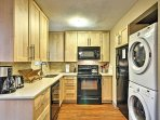 Kitchen with coffee maker, microwave oven and washer/ dryer.