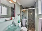 This full bathroom features a tiled walk-in shower and charming vanity.