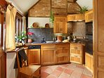 Hazelnut kitchen. Hand carved  ash folding doors lead through to living area. Open plan luxury.