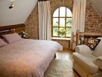 Walnut main bedroom, magnificent stone arched window giving glorious views from your super king bed.