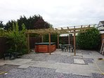 The pergola area with hot-tub and two patio areas.