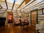 Living room with hardwood floors and open original oak beams.
