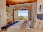 The large main bedroom with balcony doors overlooking the sea