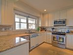 The fully equipped kitchen includes brand new appliances, granite countertops and a refreshing tile backsplash.