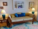 Attractive, oceanfront tropically decorated living room...but the views may prevent watching TV