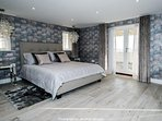 The sumptuous master bedroom with patio doors to a view across the bay