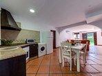 Encimera y mesa con sillas de la cocina del apartamento Hierbabuena en Hacienda Roche Viejo en Conil