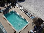 Heated pool is beachside with lounge chairs, tables, and bathrooms.