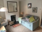 Cosy living room with wood burner, arm chair and sofa