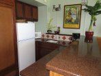 Kitchenette with full size fridge, sink, micro, granite counters, and plenty of cupboard storage.