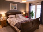 Master bedroom with kingsize bed, fitted wardrobes & ensuite with bath