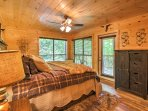 The master bedroom features a king bed and windows looking into the woods.