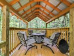 The covered deck features a fire pit, plush seating, and more!