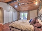 The elegant, vaulted-ceiling master bedroom boasts a king-sized bed underneath a ceiling fan, access to the back deck...
