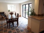 Open plan kitchen dining room with bifold doors onto patio area