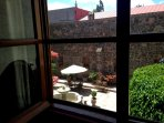 View of courtyard from LR and Master Suite. Cantera fountain, socializing area, trees and flowers.