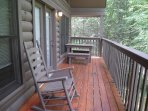 Covered side porch for relaxing with view of the forest