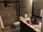 Hallway bath with granite counters and rustic waterfall faucets.