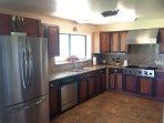 Kitchen with gas stove and stainless steel side by side refrigerator