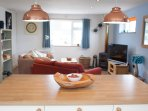 From kitchen area across breakfast bar into cosy lounge area.