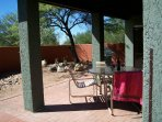 Covered patio with gas grill in background.