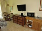 TV, drawers, sitting area, microwave, cart.