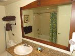 Restroom with shower/tub combo, towel rack, sink.